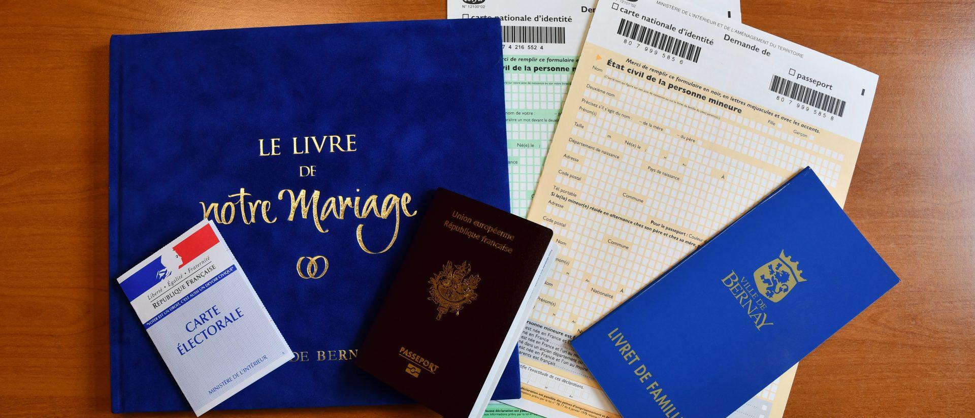 Passeport carte d'identité livret de famille livre de mairiage et formulaires posés sur une table