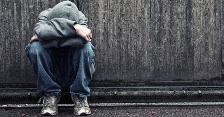 un homme en sweat et jean assis au sol la tête entre ses bras